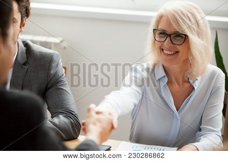 Smiling Attractive Mature Businesswoman Handshaking Businessman At Meeting Negotiation, Happy Hr Sen