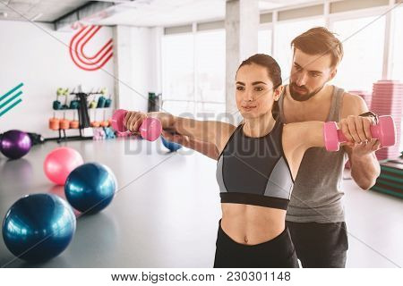 Two people are standing in the finess room. The guy is helping his girfriend to do push ups with dumbells. Cut view stock photo