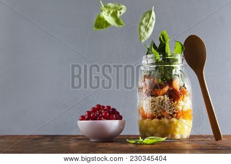 Mason jars with hot Salad: Chickpeas, arrots, quinoa, roasted Pumpkin and spinach. Ripe red currants . Healthy Lunch. falling leaves of basil stock photo