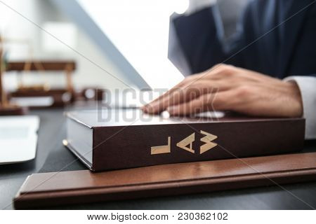 Lawyer holding hand on juridical textbook at table in office stock photo