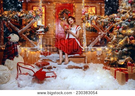 Smiling Santa girl holds a gift box in her hands and poses near the house of Santa, decorated with festive lights. Christmas and New Year concept. stock photo