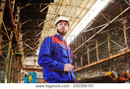 Young man working with a wrench in the hands of a plant or production stock photo