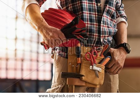 Closeup of bricklayer hands holding hardhat and construction equipment. Detail of mason man hands ho