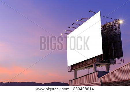 Empty large white advertising billboard on top of the building and sky background in sunset time. For design and advertisement concept stock photo