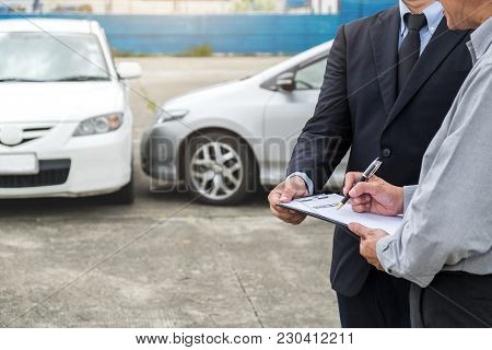 Insurance Agent Examine Damaged Car And Customer Filing Signature On Report Claim Form Process After