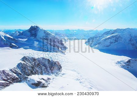 Mountain peaks ridge with Aletsch glacier in winter Swiss Alps helicopter view stock photo