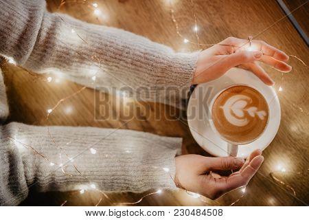 Girl holding coffee in hands over light bokeh background. Overhead shot. stock photo