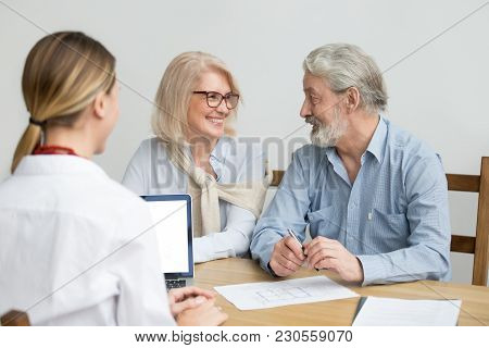 Happy Senior Couple Deciding Discussing New House Purchase At Meeting With Agent, Smiling Older Aged
