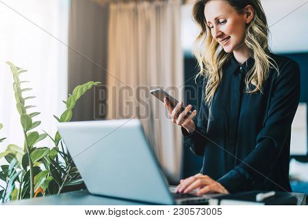 Young smiling businesswoman in black blouse is standing indoor, working on computer while using smartphone. Girl freelancer works at home. Online marketing, education, distance work. Social network. stock photo