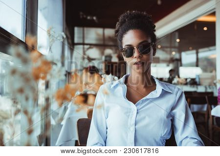 Elegant classy Brazilian girl in sunglasses is sitting inside of a luxury restaurant; young black female in a bright shirt and dark glasses is waiting for her food order in a luxurious cafe stock photo
