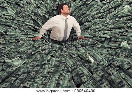 Businessman swallowed by a big black hole of money. Concept of failure and economic crisis stock photo