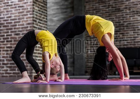 Kids yoga female teacher training a child girl standing in wheel pose working out in stylish sports studio. stock photo