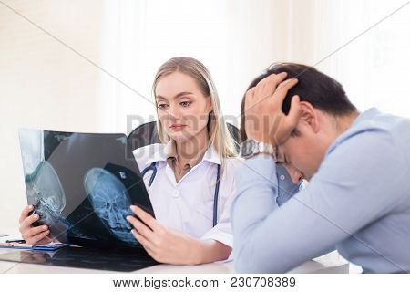Attractive female doctor showing x-ray films to patient at clinic. Medical and Health care concept. stock photo