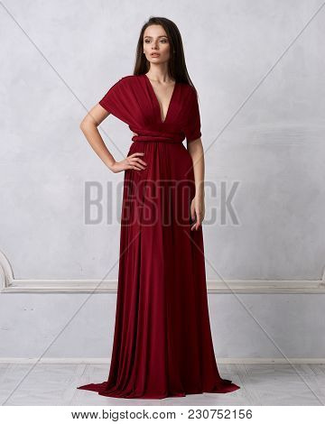 Beautiful long haired young woman dressed in stylish cherry red bandeau maxi dress posing against white wall on background. Elegant brunette female model demonstrating evening outfit in studio. stock photo