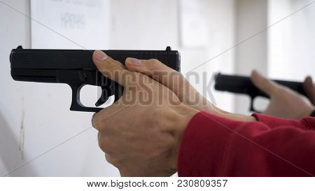 Instructor teaches a man to handle a weapon or gun. Close up of male hands with gun while training with instructor. Close up of man's hand reloading gun. stock photo