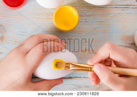 Preparation for Easter set for dyeing eggs on rustik background with plate of candy children hands, babycraft handmade Easter eggs stock photo