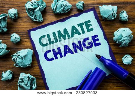 Writing text showing Climate Change. Business concept for Global Planet Warming Written on sticky note paper, wooden background marker folded yellow paper meaning thinking stock photo