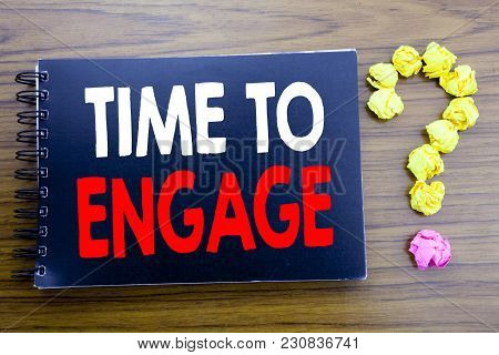 Handwritten text showing Time To Engage. Business concept writing for Engagement Involvement Written on notepad paper, wooden background in office view with question mark on the end. stock photo