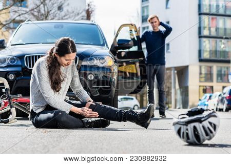 Full length of a young female bicyclist fallen down on street with serious injuries after traffic ac