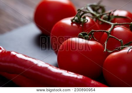 Spring composition of tomato bunch and hot pepper on piece of board over wooden background, top view, closeup, selective focus, shallow depth of field. Perfect vegetable stilllife. Delicious healthy appetizer. Fresh ingredient. Healthy food concept. stock photo