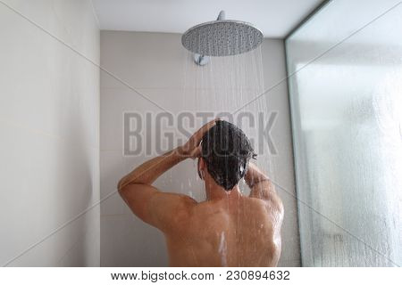 Man taking a shower washing hair under water falling from rain showerhead. Showering person at home
