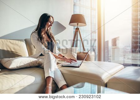 Elegant young female business woman using a laptop sitting on a sofa at home. stock photo