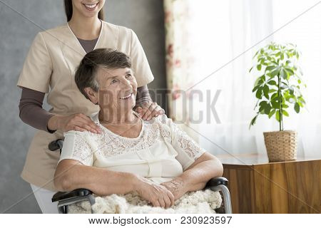 Smiling caregiver and disabled senior woman spending time together in a hospice stock photo