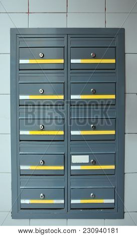 grey steel modern lockable mailboxes in a tiled exterior wall with yellow and white labels stock photo