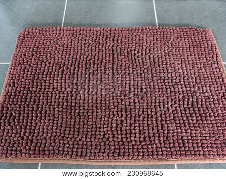 Soft brown door mat on the tile floor in front of the door,modern house in the city. stock photo