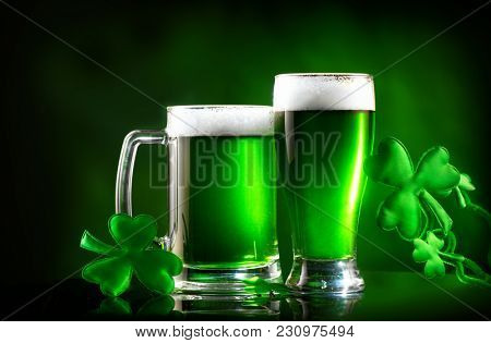 St. Patrick's Day Green Beer pint over dark green background, decorated with shamrock leaves. Patrick Day pub party, celebrating. Glass of Green beer close-up. Border art design, Wide format banner stock photo