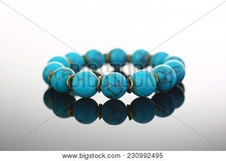 Bracelet of bijouterie jewelry made of turquoise and gold on a gray black background stock photo