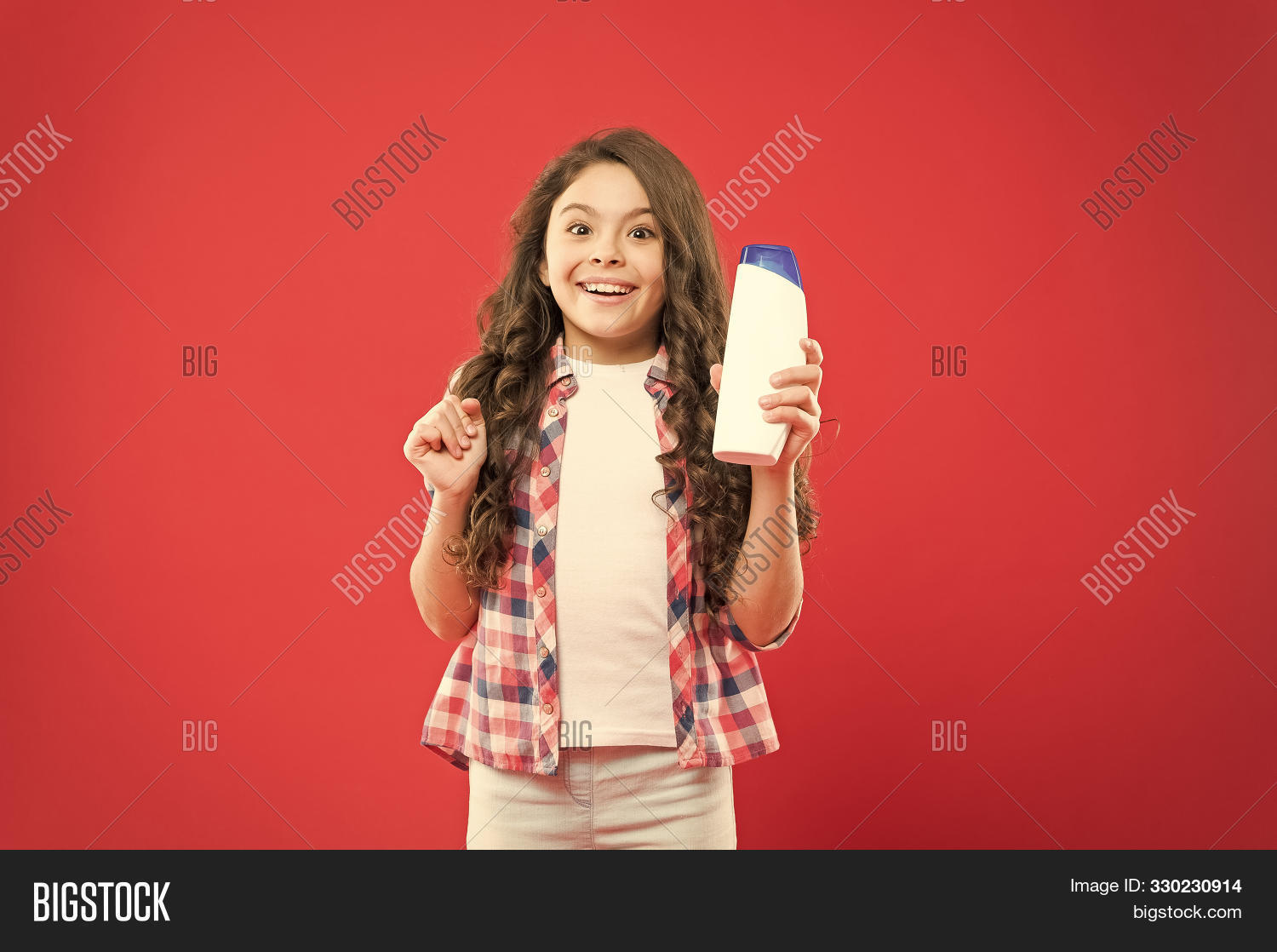 Hygiene habits for kids. Happy little girl holding gel or shampoo bottle for personal hygiene on red background. Small child with long hair smiling with hygiene product. Everyday hygiene and health.