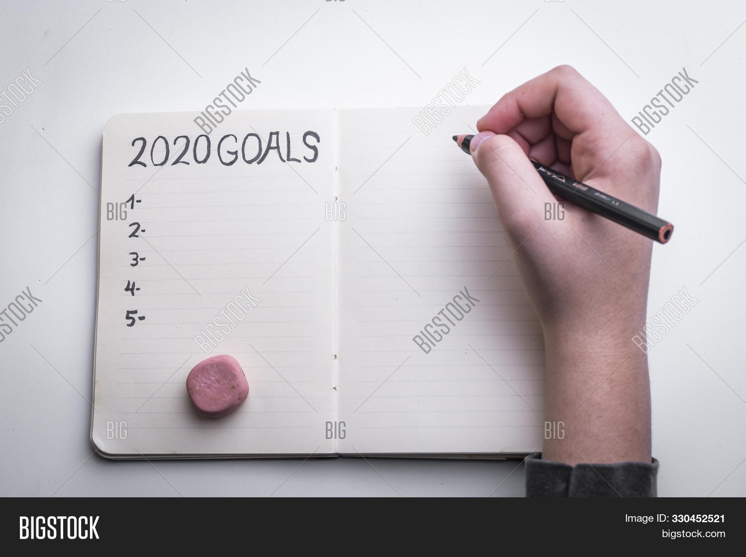 New Year 2020 target, action text in notepad with woman's hands and white background.