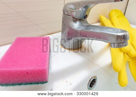 Sponge and gloves for washing dirty faucet with limescale, calcified water tap with lime scale on washbowl in bathroom, house cleaning concept stock photo