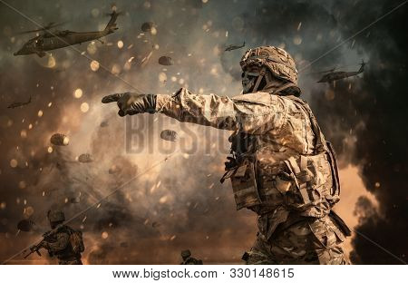 Military helicopter and forces between fire and dust in the battlefield stock photo