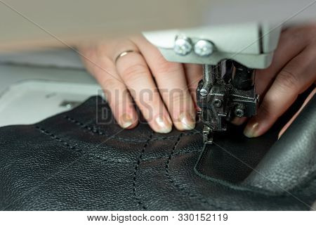 The process of sewing shoes on a sewing machine. Shoe production. stock photo