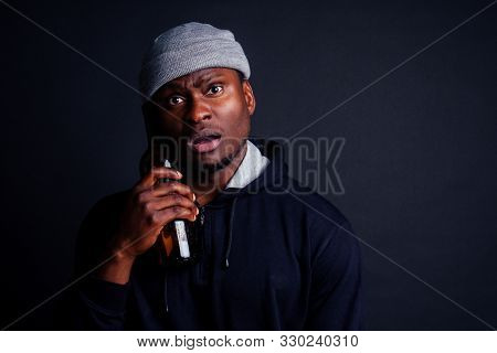 african american man holding a bottle of wine and feeling headache shit in studio black background.bum homeless drowning out the pain stock photo