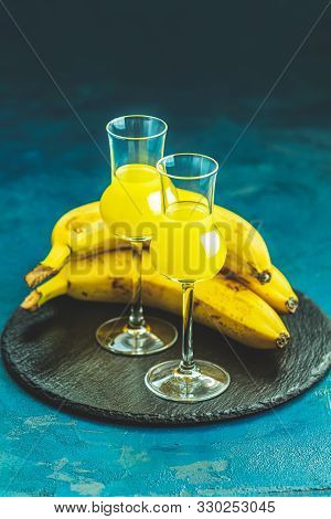 Banana flavoured liqueurs, which French call creme de banana, in  grappas wineglass on dark blue concrete surface. European aperitif drink. Selective focus, shallow depth of the fields, copy space. stock photo