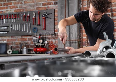 man work in home workshop garage with steel file rasp, filing metal pipe on the workbench full of wrenches, diy and craft concept stock photo