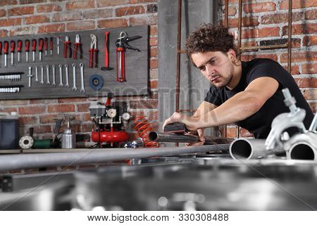 man work in home workshop garage with sandpaper sanding surface of metal pipe on the workbench full of wrenches, diy and craft concept stock photo