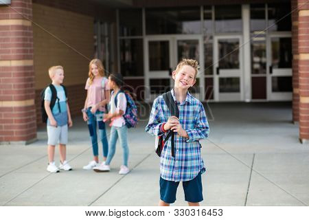 Handsome pre-adolescent teen boy student hanging out with friends after school. Selective focus on the smiling boy student standing outside the school building with friends in the background stock photo
