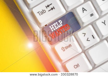 Writing note showing Help Wanted. Business photo showcasing An ad in the paper an employer places to find a new employee White pc keyboard with note paper above the white background. stock photo