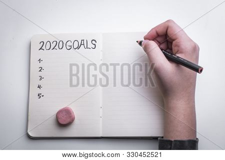 New Year 2020 target, action text in notepad with woman's hands and white background. stock photo