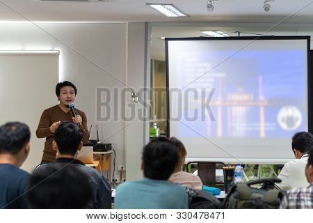 Asian Speaker or lecture with casual suit on the stage in front of the room presenting with the screen in the conference hall or seminar meeting room, business and education concept stock photo