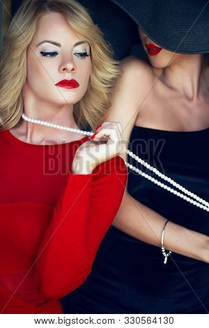 Lesbian lover bonding sensual blonde woman in red by pearls stock photo