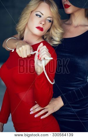 Sinful blonde woman in red with lesbian lover foreplay, lust stock photo