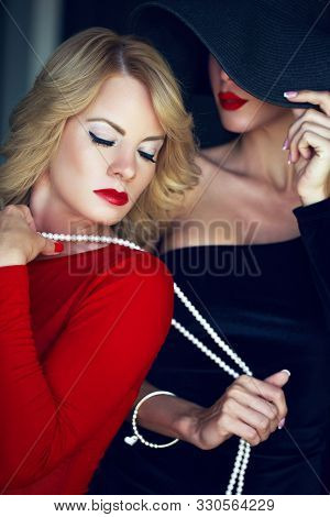Lesbian lover holded by pearls indoors, women in red and black stock photo