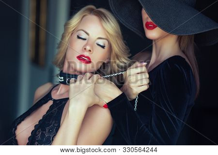 Sensual blonde woman in underwear holded by lesbian lover on chain, lust stock photo