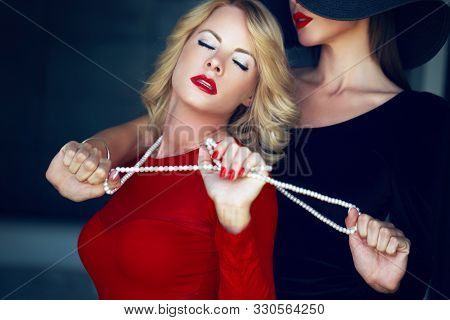 Sensual woman in red with lesbian lover, lust and pearls stock photo