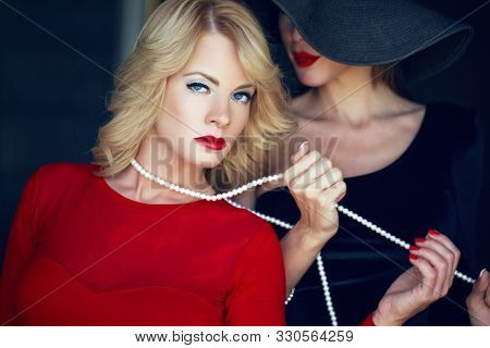 Blonde woman in red bonded by lesbian lover on pearls, seduction stock photo